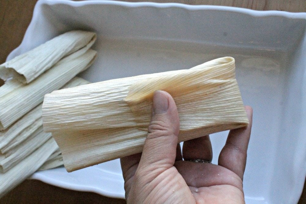 Hand holding a folded tamal.