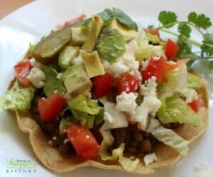 Lentil Tostadas topped with lettuce, tomatoes, avocado, and queso fresco.