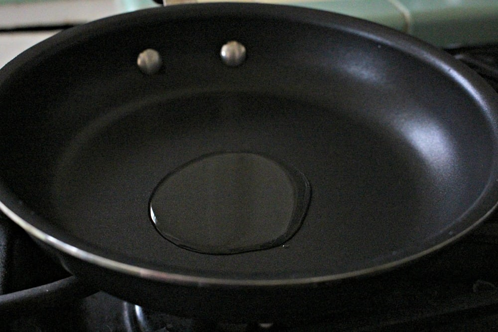 Oil heating up in a skillet.