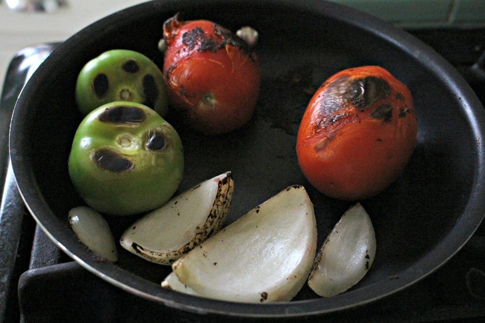 Tomatoes, Tomatillos, Onion charring in a skillet