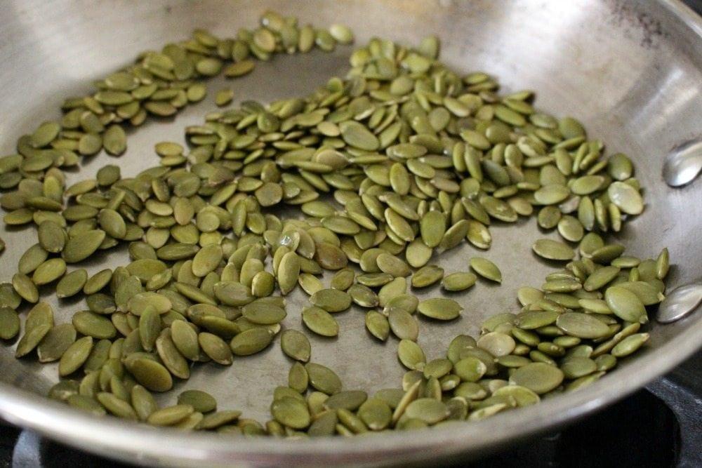 Toasting pepitas in a metal skillet