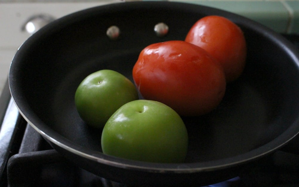 2 tomatoes and 2 tomatillos cooking in a skillet.