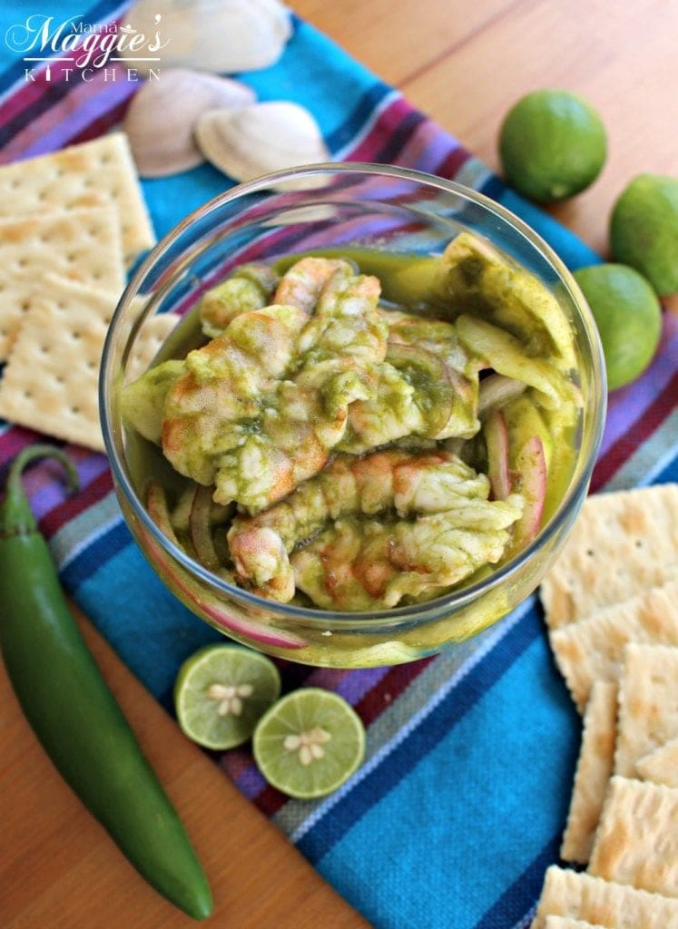 Aguachiles, or Shrimp in Spicy Green Chile Sauce, surrounded by crackers, lime and decorative Mexican tablecloth