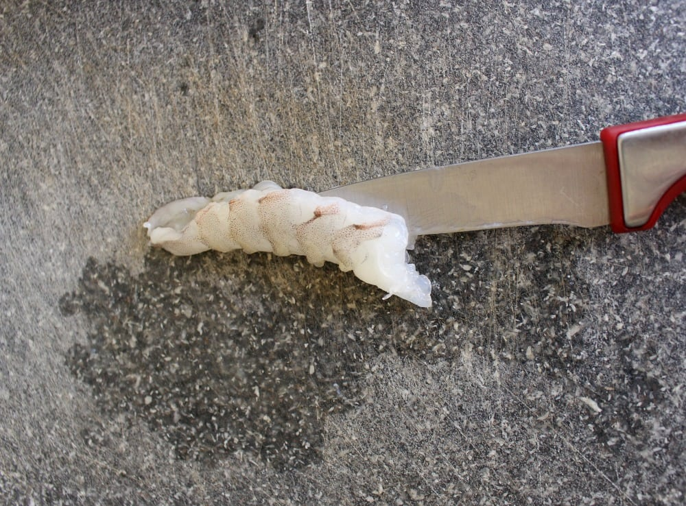 A knife cutting shrimp around the edges.