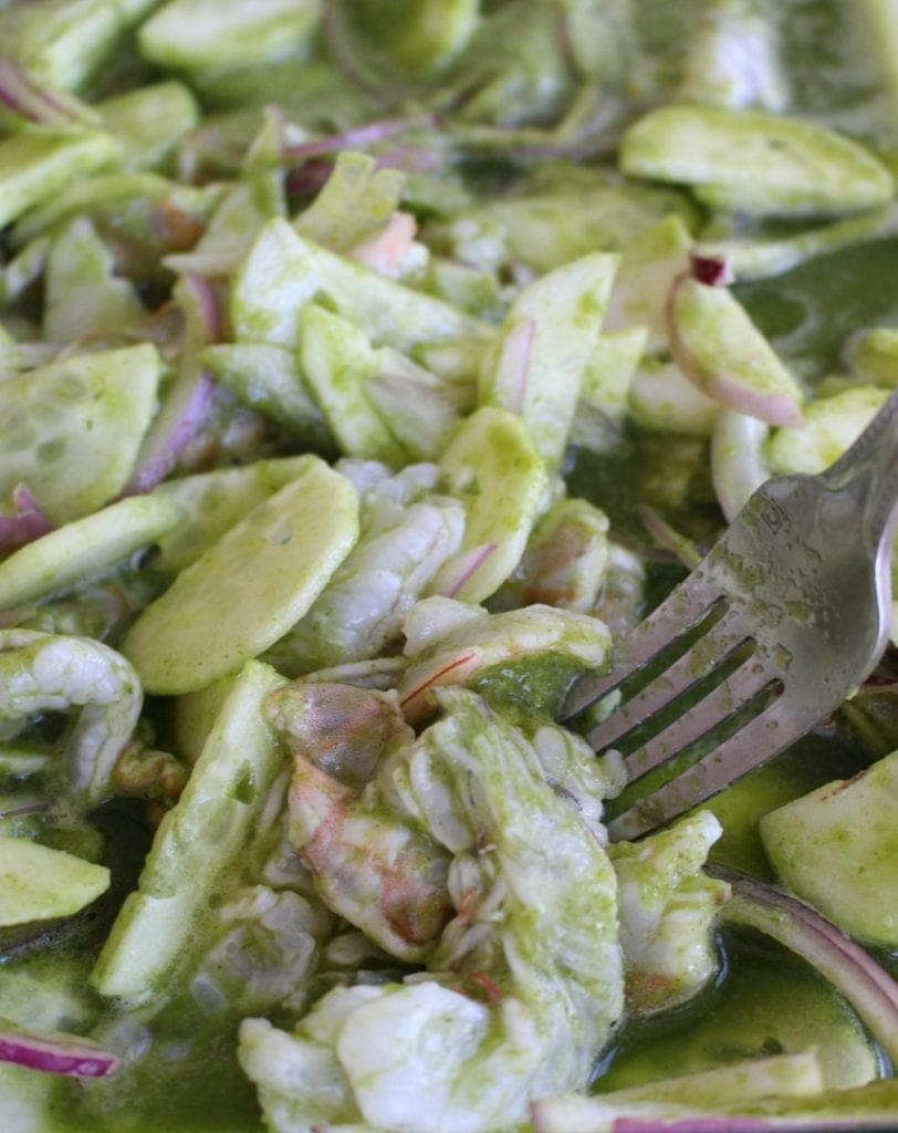 Fork mixing Aguachiles de Camaron in a glass container.