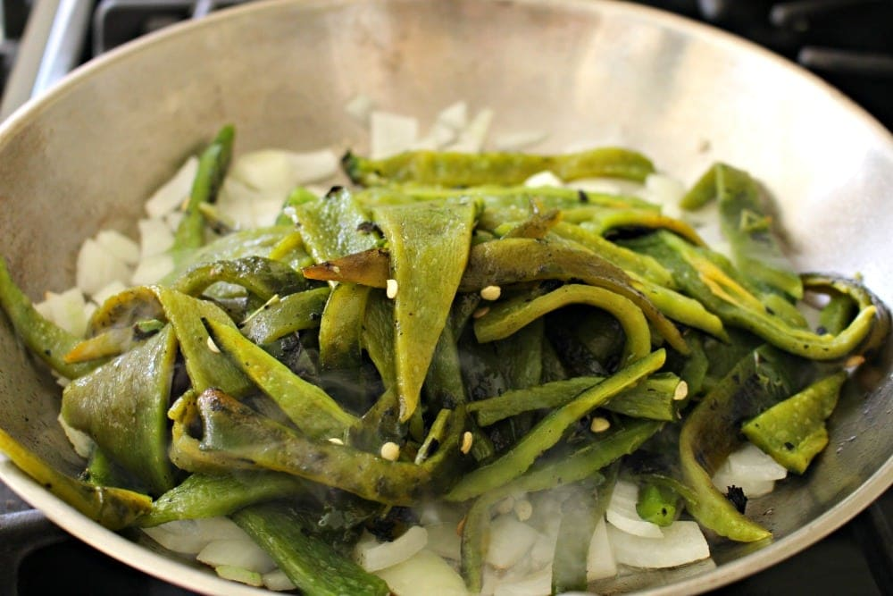Rajas on top of onions in a skillet