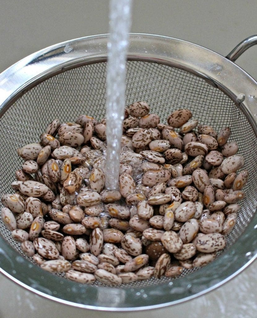 Faucet water rinsing pinto beans in a metal strainer