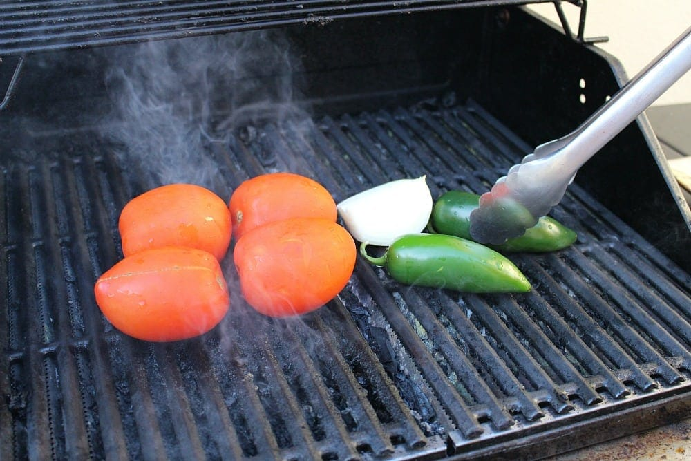 Tongs putting jalapenos and onions on the grill next to the tomatoes