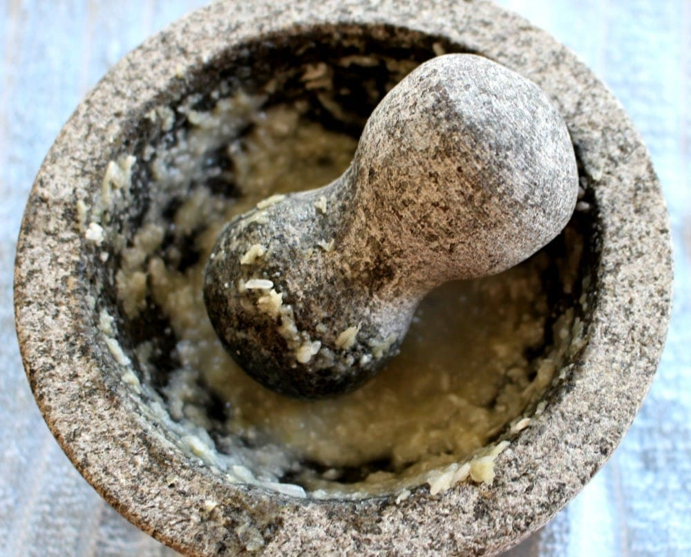 Mixing garlic and rice in a molcajete