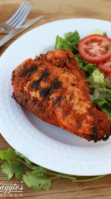 Pollo Adobado Mexican Chicken Adobo on a white plate with a green lettuce and tomoato