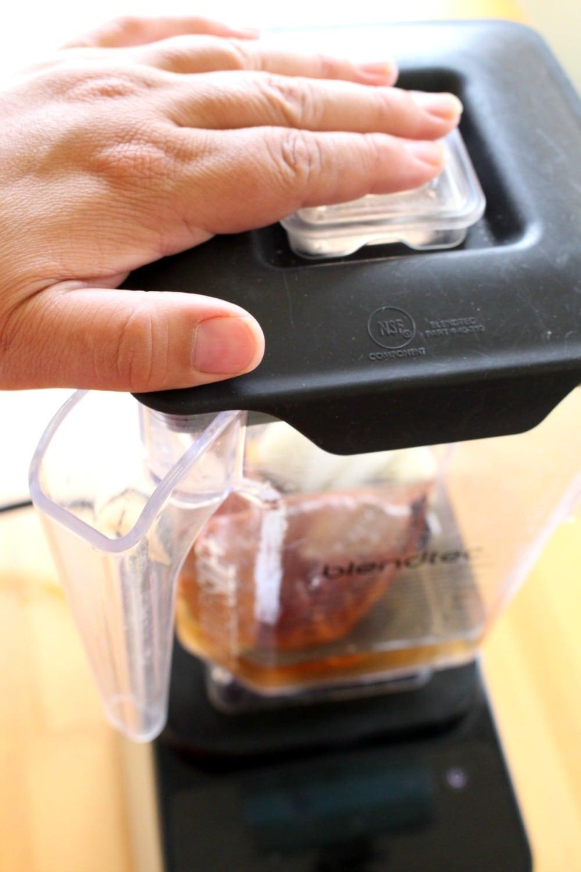Hand holding down blender lid