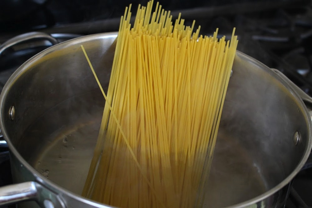 Dried spaghetti standing in a pot of boiling water