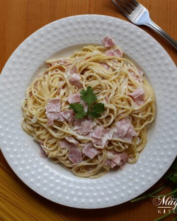 Espagueti a la Crema, Spaghetti with Ham and Cream Sauce, on white plate surrounded by dried pasta and a fork