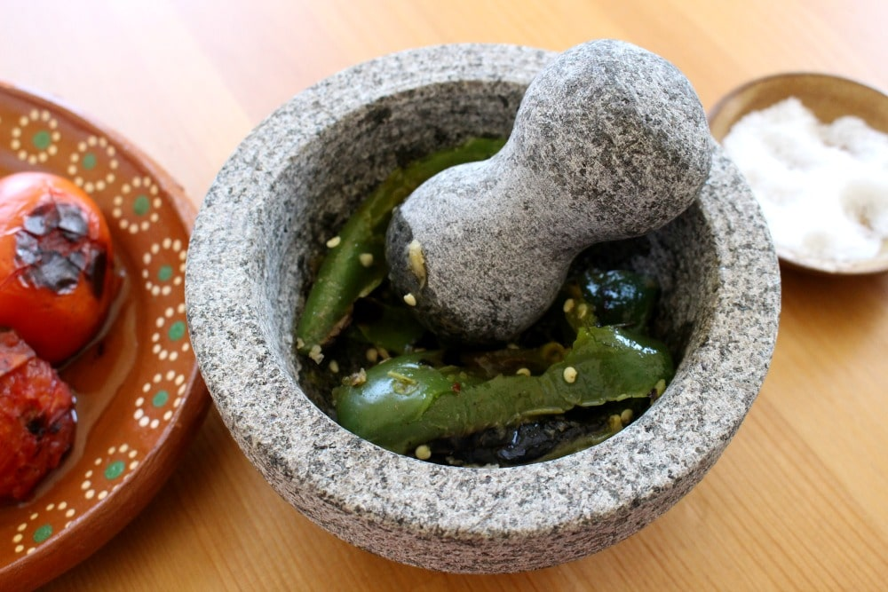 Jalapenos in a molcajete with a pestle surrounded by decorative Mexican plates.