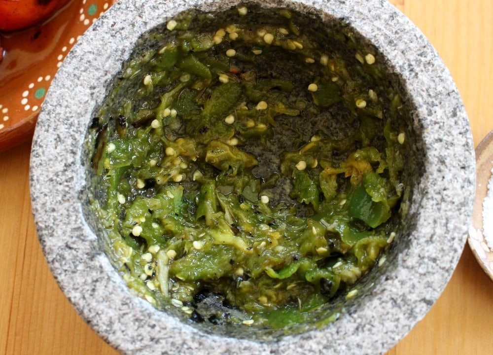Mashed jalapeno in a molcajete, or mortar and pestle.