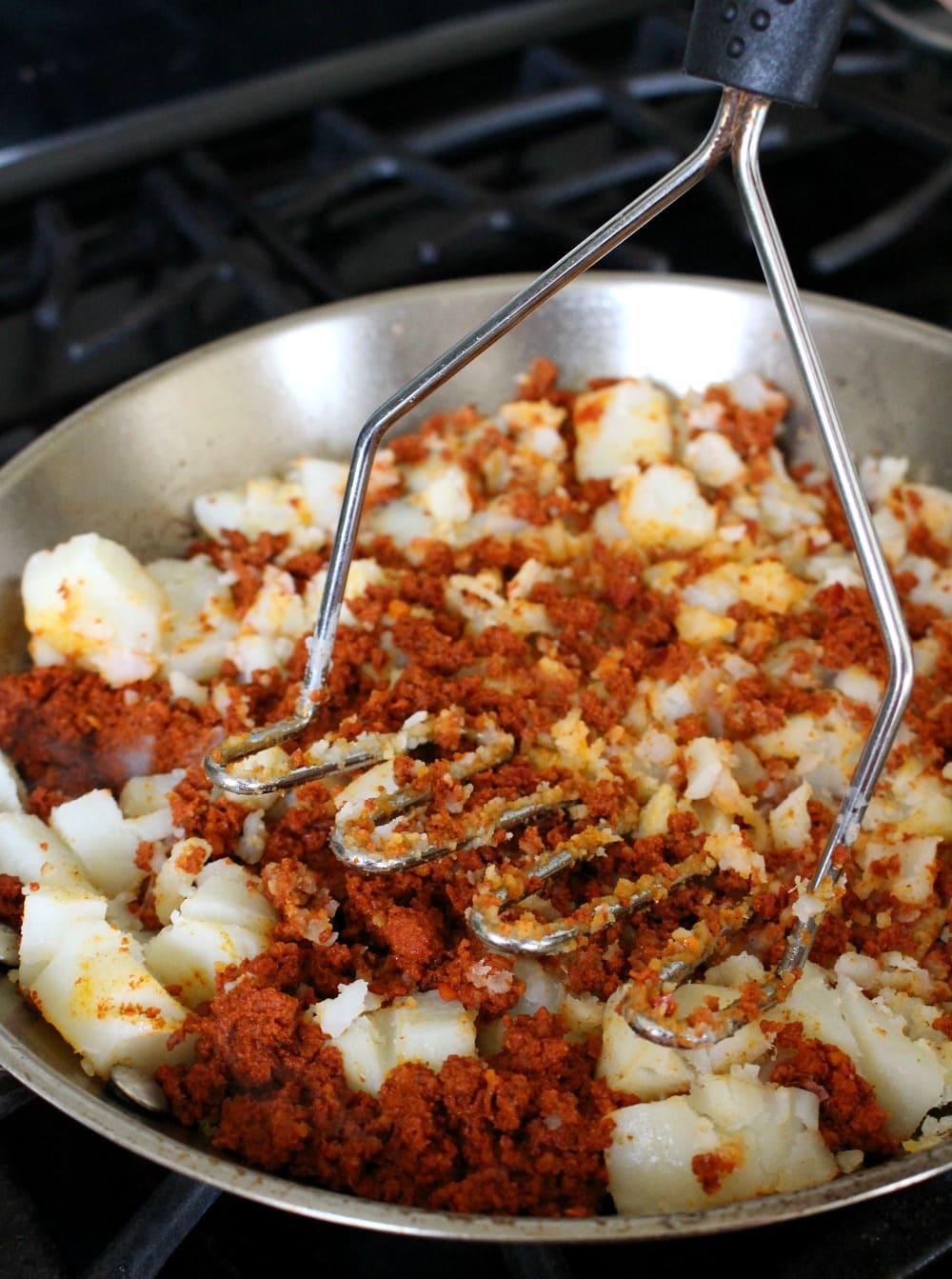 Mashing potatoes and chorizo with a potato masher