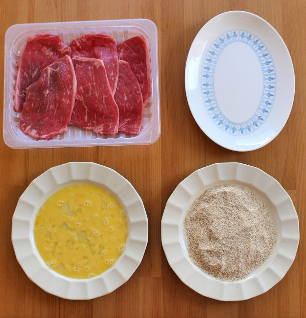 Meat slices on the far top left corner. Oval white plate on the far top right corner. Plate with egg mixture on the bottom left corner. Plate with breadcrumbs on the bottom right corner.