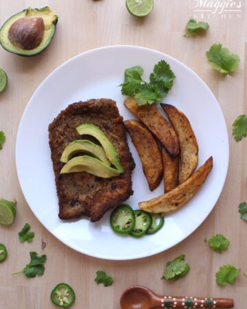 Milanesa de Res and homemade french fries sitting on a white plate. The meat is topped with avocado and surrounded by cilantro leaves.