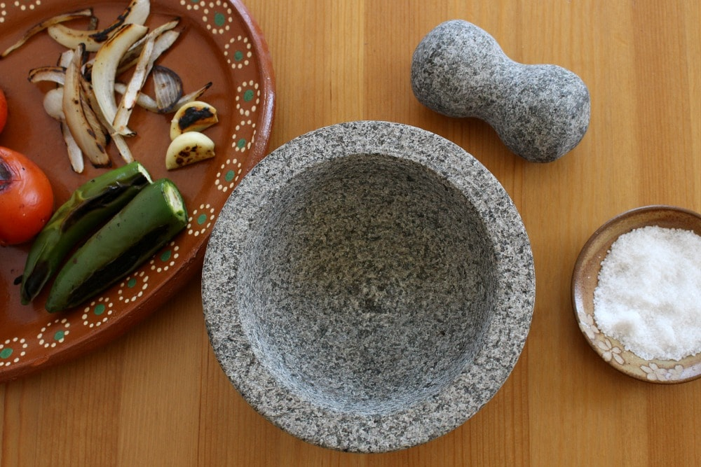 Empty molcajete or mortar and pestle surrounded by the salsa ingredients and salt