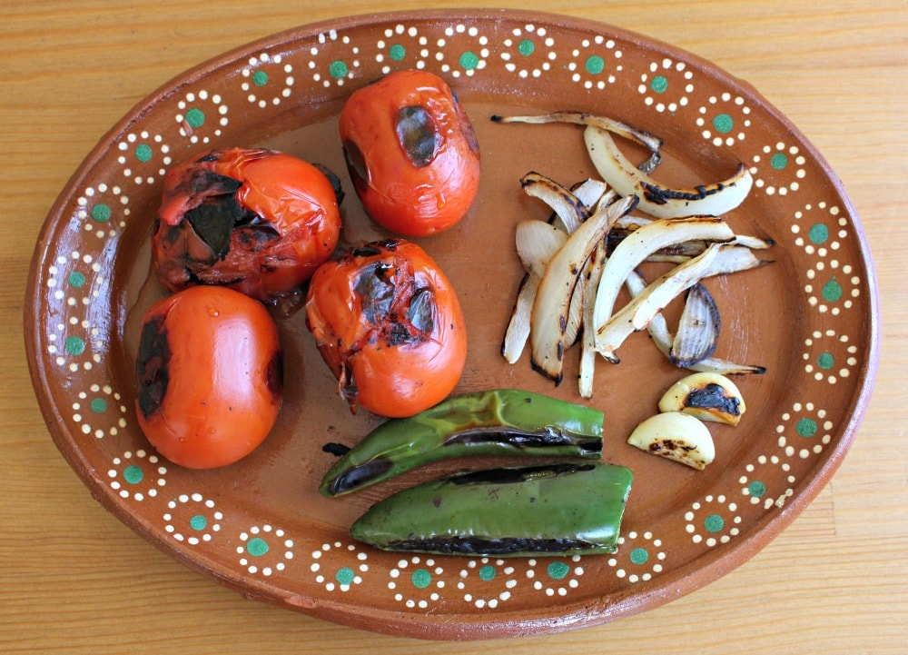 Roasted Ingredients for salsa on a decorative Mexican plate.