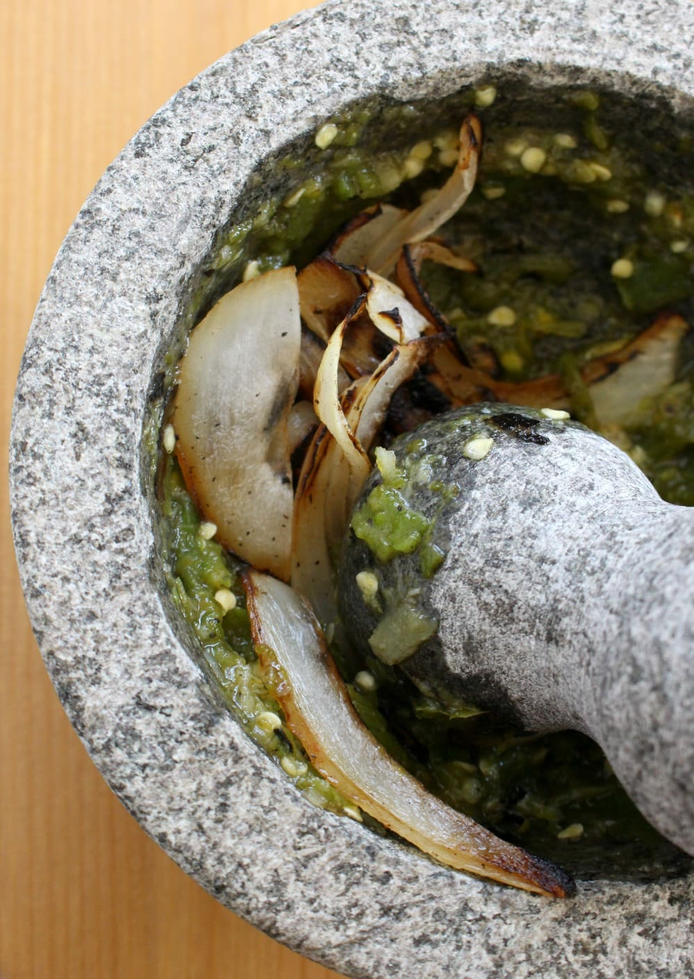 Roasted onions in a gray molcajete.