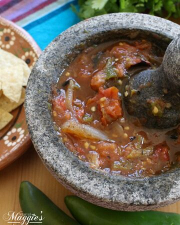 Roasted Tomato Salsa in a volcanic rock molcajete surrounded by jalapenos, chips, and a decorative Mexican cloth.