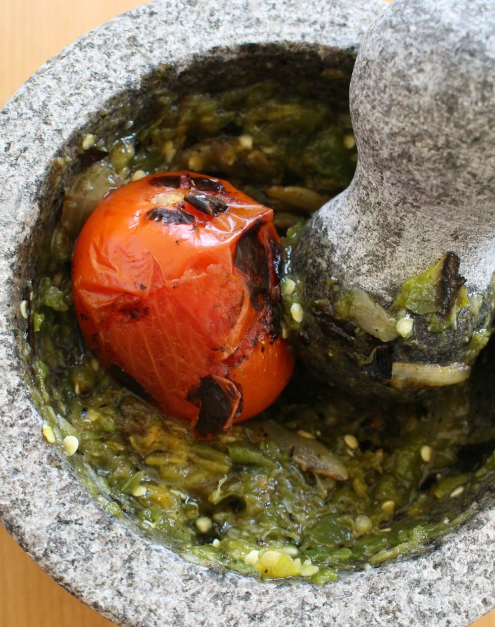 Roasted tomato in molcajete with the pestle and mashed jalapeno.