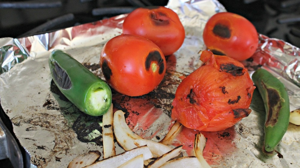 Roasted tomatoes and jalapenos roasting on aluminum foil.
