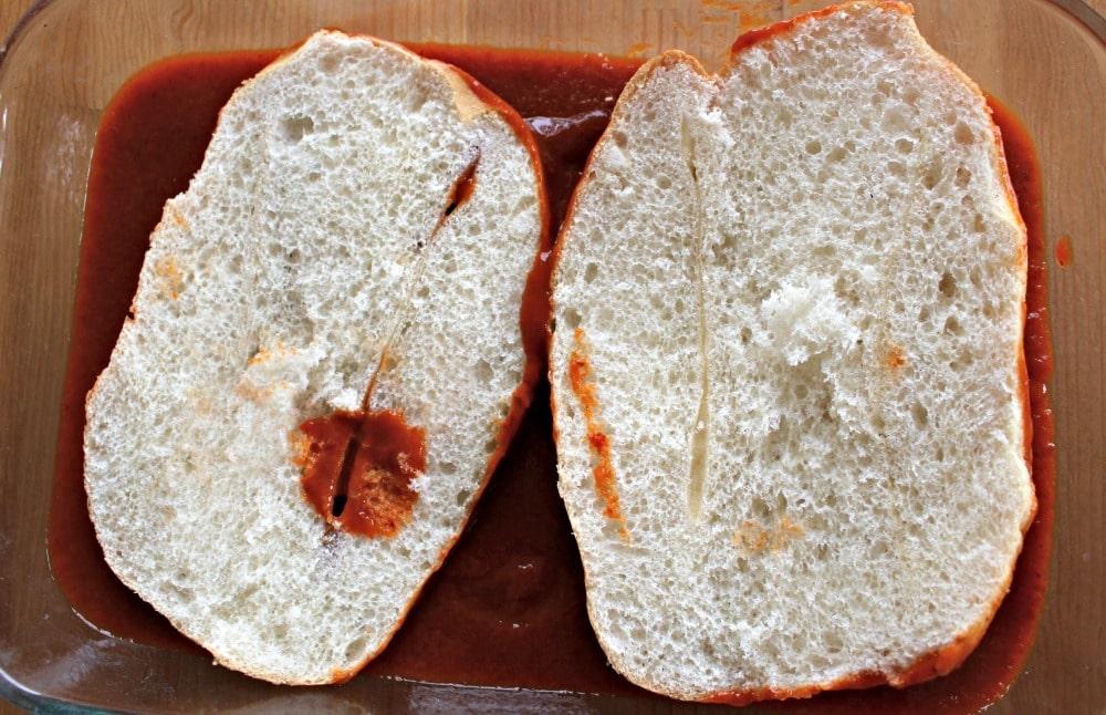Mexican telera bread cut in half and dunked in guajillo sauce