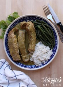 Costillas en Salsa Verde, or Ribs in Mexican Green Salsa, served on a blue plate with rice and green beans.