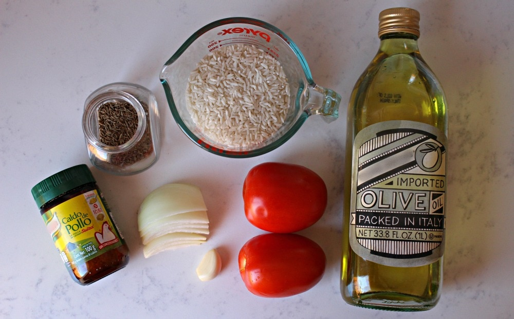 Ingredients for Mexican Rice on a white marble surface.