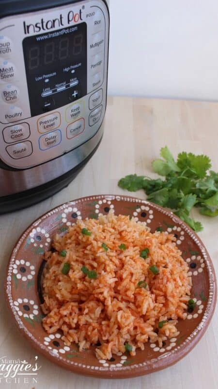 Mexican rice next to an instant pot and cilantro leaves.