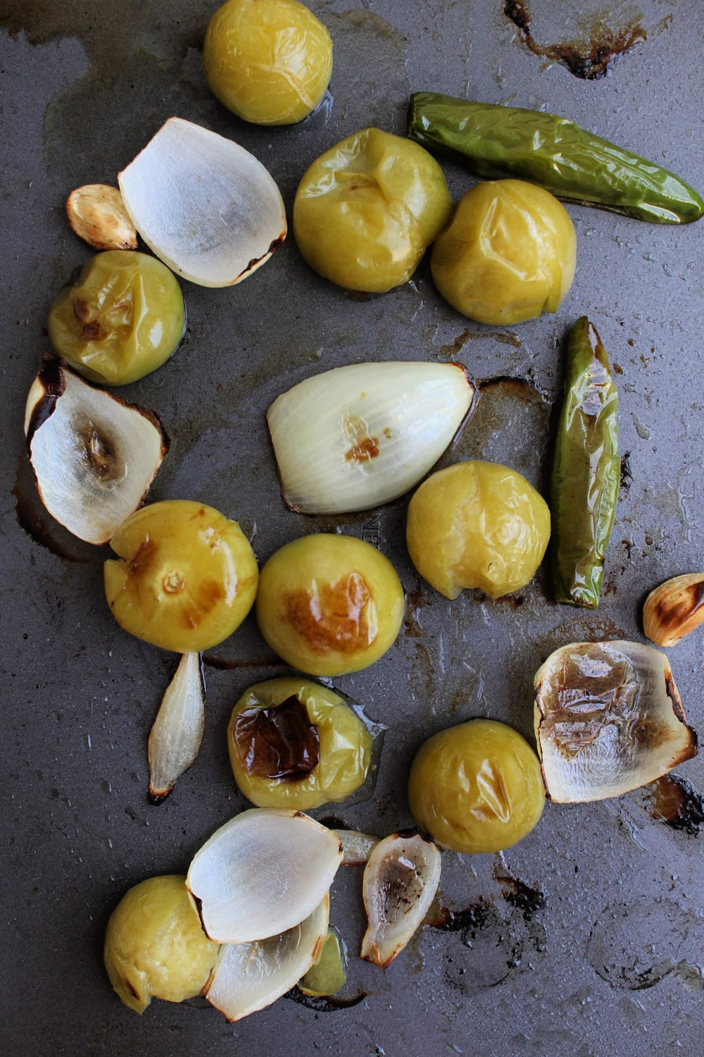 Roasted tomatillos and onions on a baking sheet.