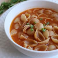 Sopa de Conchas, or Mexican Shell Pasta Soup, in a white bowl and topped with a few slices of green onions.