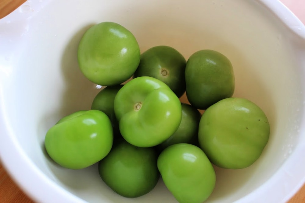 White bowl filled with green tomatillos.