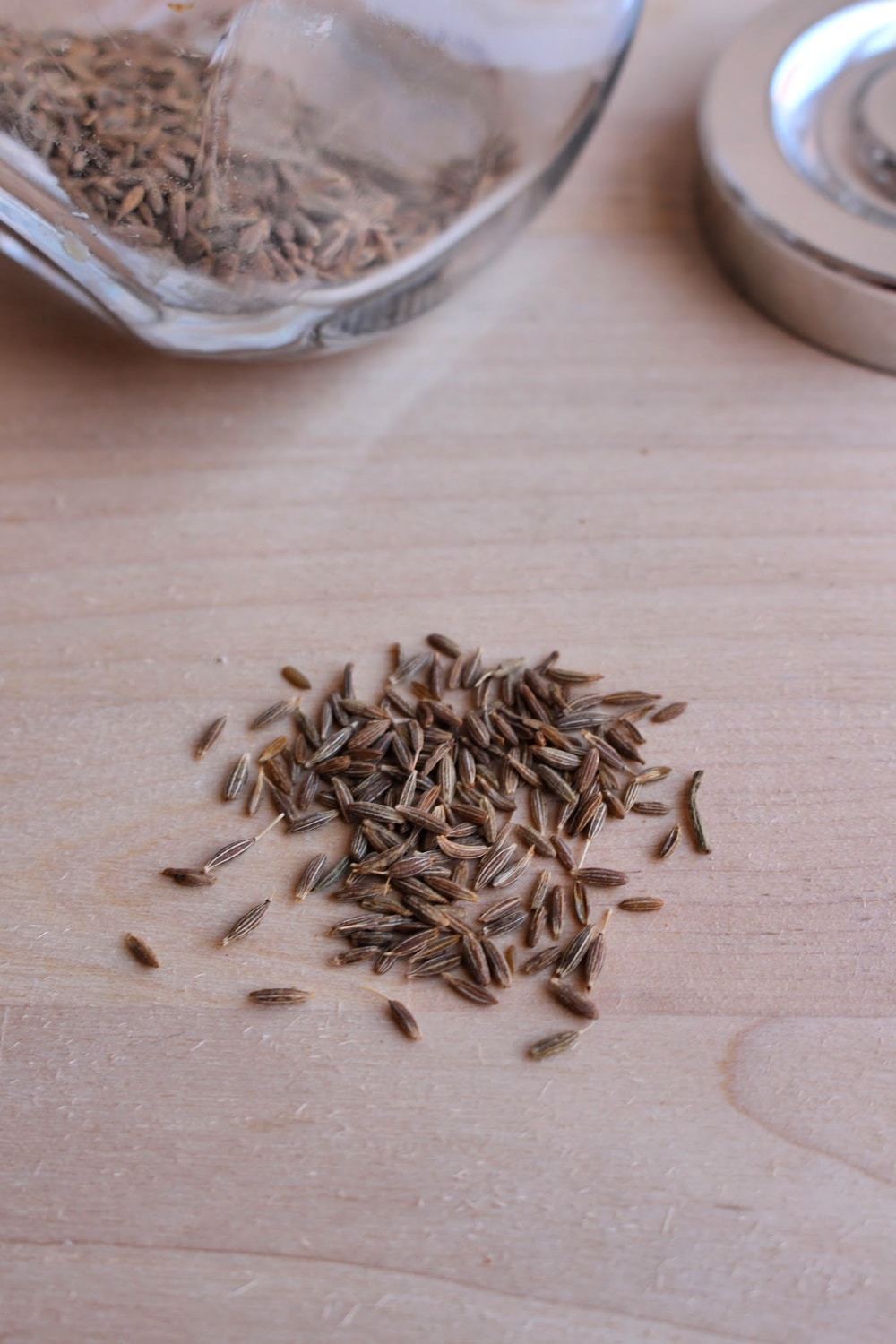 Whole cumin on a wooden surface.