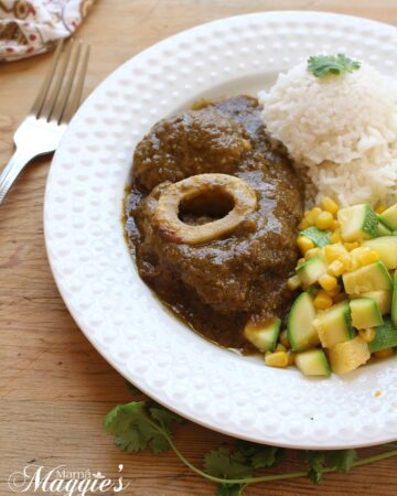 Chamorro en Salsa Verde, or Beef Hind Shank in Mexican green sauce, on a white plate with veggies and rice on a wooden surface next to a fork.