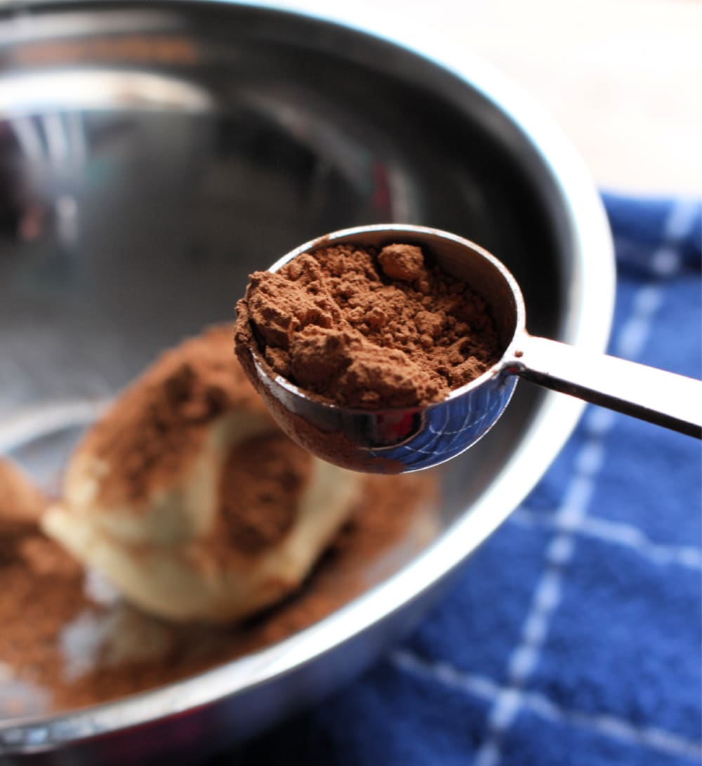 Measuring spoon with cocoa powder next to a metal bowl.