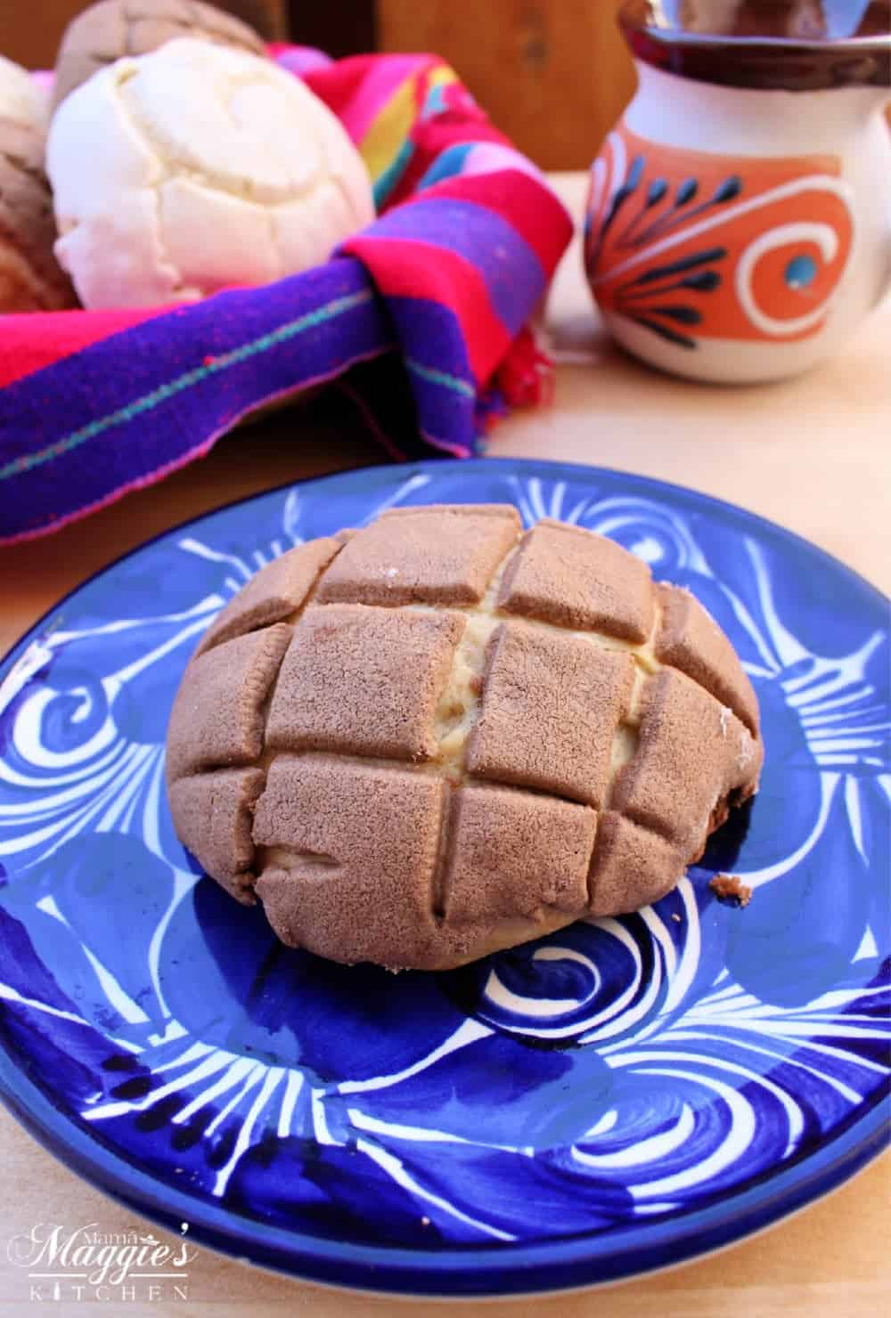 Chocolate concha on a blue plate with a decorative Mexican basket in the background holding more conchas.
