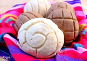 Mexican Sweet Bread Conchas in a decorative and colorful tablecloth.