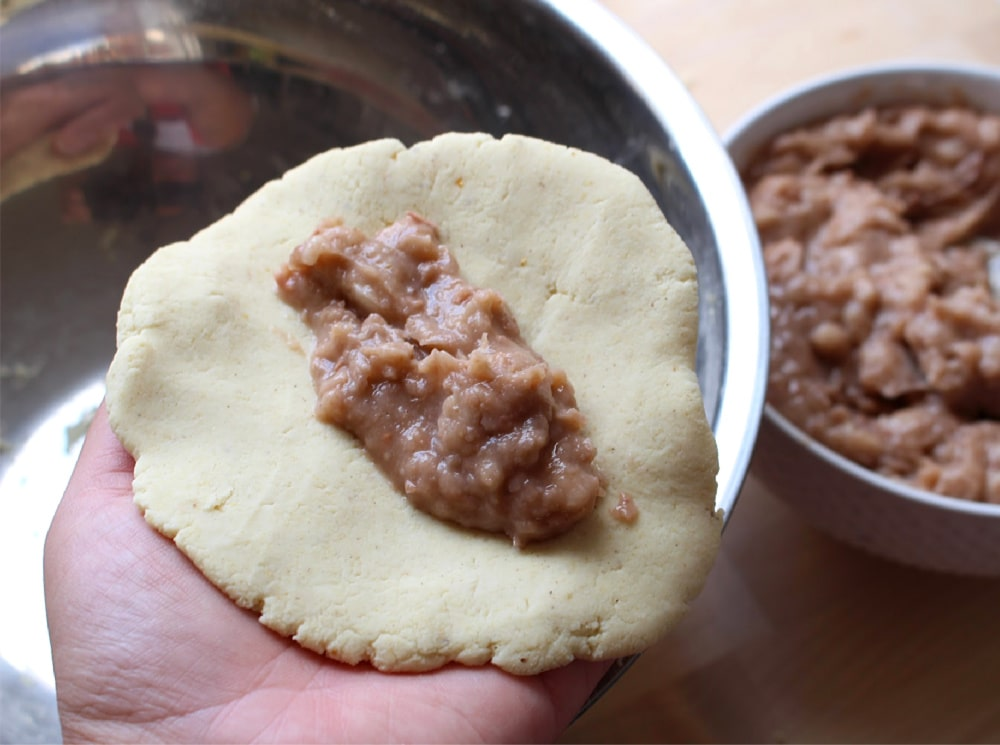 Refried beans in the center of the masa held by a hand.