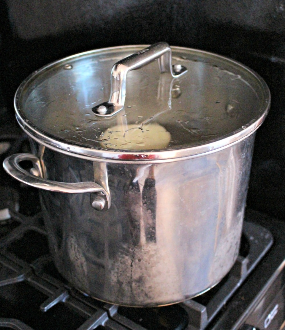 A large pot on a black stove cooking.