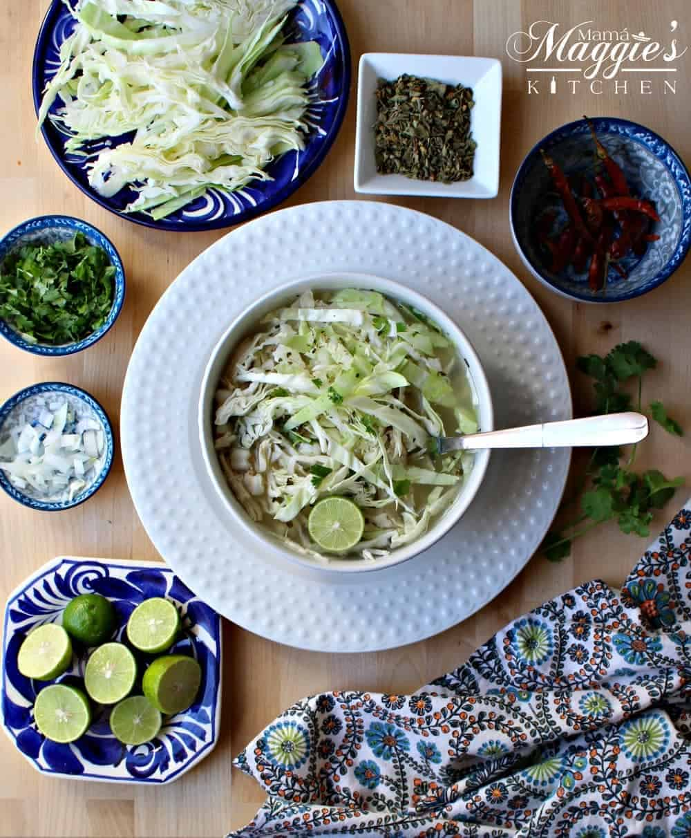 Pozole Blanco, or Chicken Pozole, in a white bowl surrounded by all the toppings for this Mexican soup.