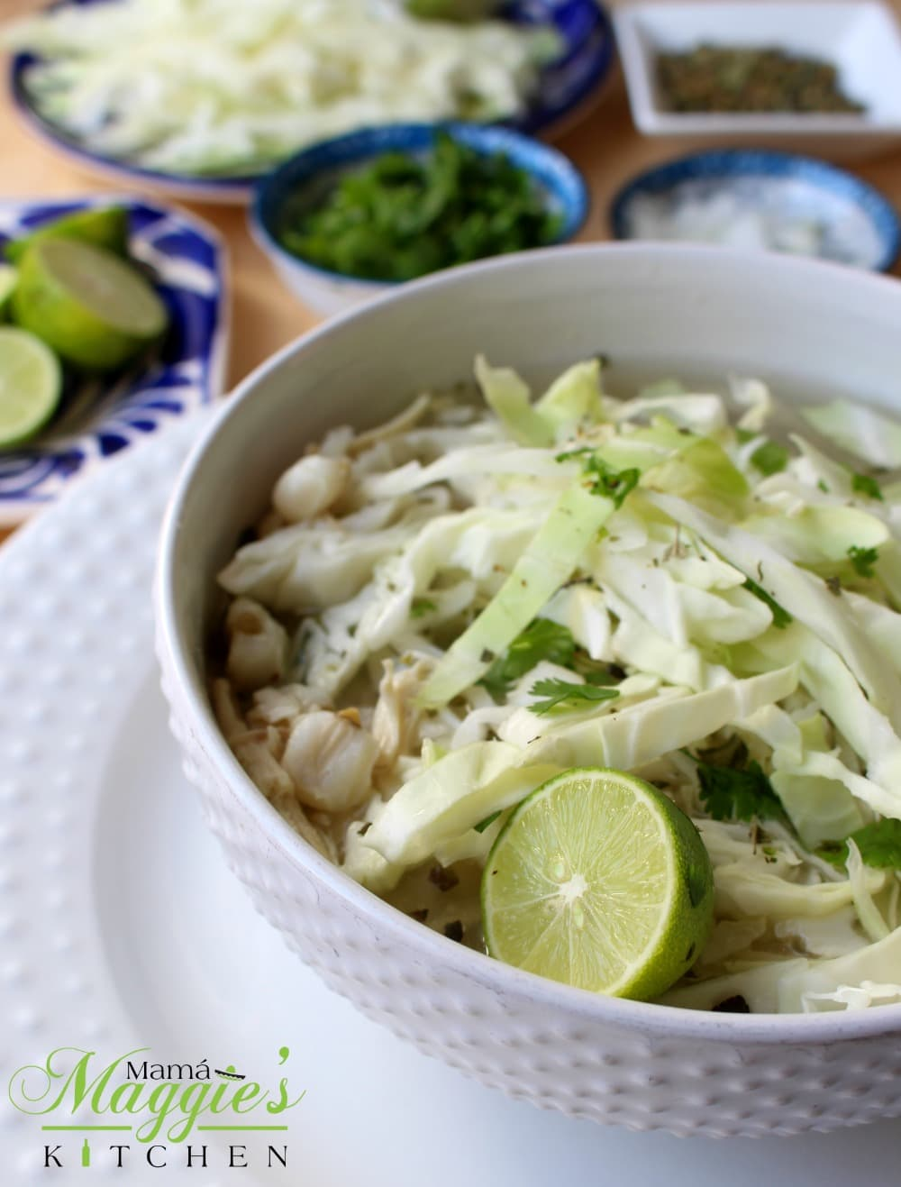 A white bowl of Pozole Blanco (Chicken Pozole) surrounded by the toppings.