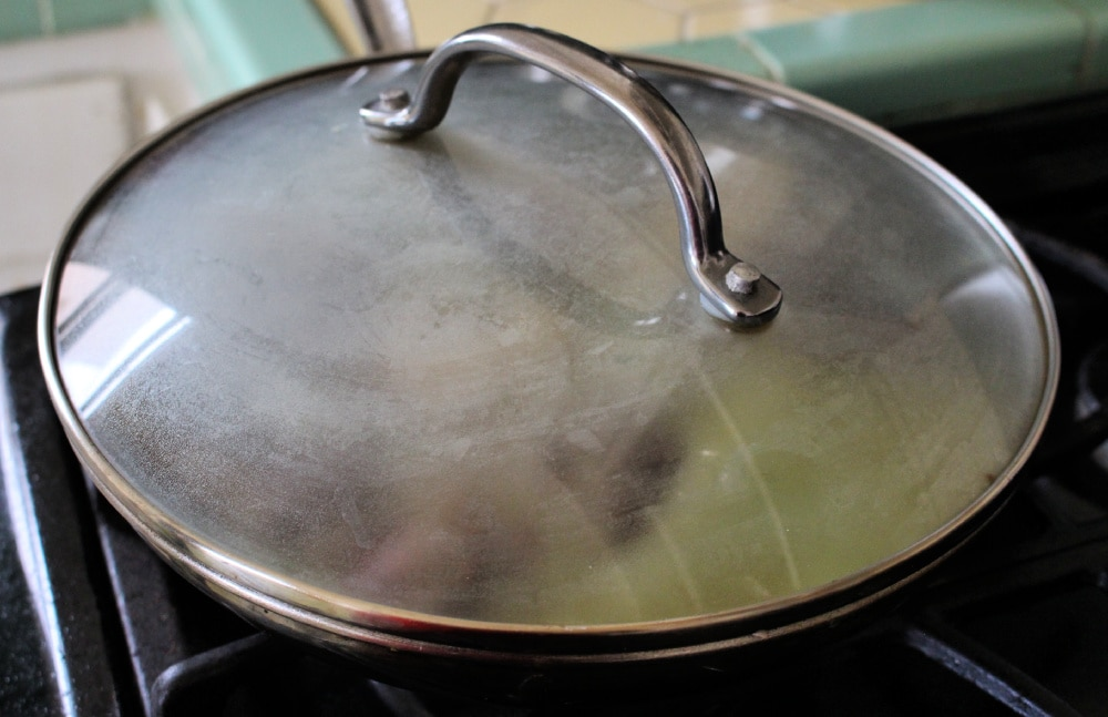 Lid on a metal skillet with beef shanks in salsa verde inside.