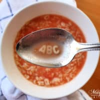 Spoon holding ABC over a bowl full of Sopa de Letras, or Mexican Alphabet Soup.
