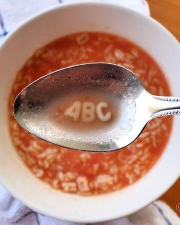 Spoon holding ABC over a bowl full of Sopa de Letras, or Mexican Alphabet Soup.