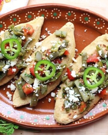 Tlacoyos topped with cactus salad on a decorative Mexican plate and cilantro.