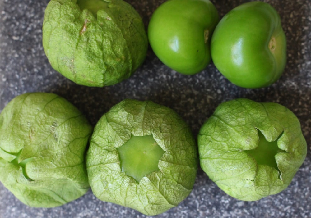 Six tomatillos on a black granite counter some with the husks still on.