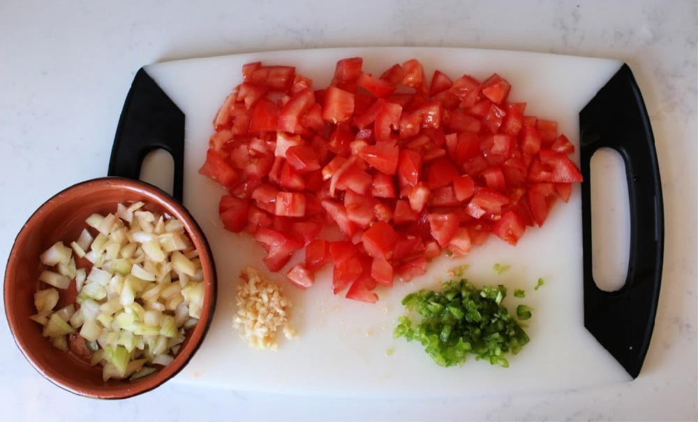 Cutting board with diced tomatoes, jalapenos, garlic, and onion.